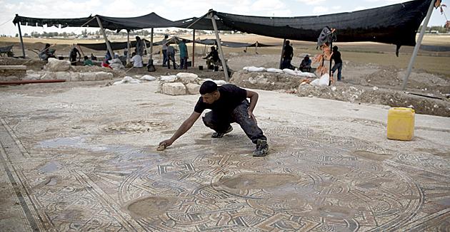 אַ ישׂראלדיקער אַרכעאָלאָג באַקוקט אַ מאָזאַיִק געשאַפֿן מיט 1500 יאָר צוריק לעבן קיבוץ בית-קמה אינעם נגבֿ