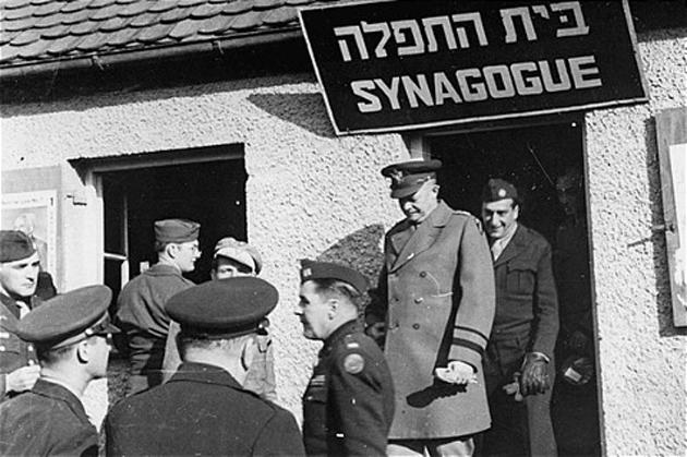 """גענעראַל אײַזנהאַוער גייט אַרויס פֿון דער לאַגער־שיל בשעת זײַן אָפֿיציעלן טור פֿונעם די־פּי־לאַגער """"נײַ פֿרײַמאַן"""" אין 1945"""