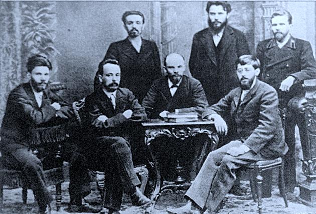 """יולי מאַרטאָוו (זיצט רעכטס) צווישן דער גרופּע פֿון דעם """"פֿאַראיין פֿאַרן קאַמף צו באַפֿרײַען דעם אַרבעטער־קלאַס"""" (1897)"""