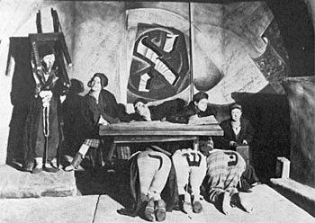 """אַ סצענע פֿון דער פּיעסע """"חדר"""" אויף אַן אנטי־רעליגיעזער טעמע, אין דעם ווײַסרוסישן ייִדישן מלוכה־טעאַטער, מינסק, 1920—1930ער יאָרן"""