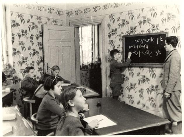 קינדער־פּליטים פֿון דײַטשלאַנד, בעת אַ ייִדיש־לעקציע אין דער מעדעם־סאַנאַטאָריע, בערך 1938